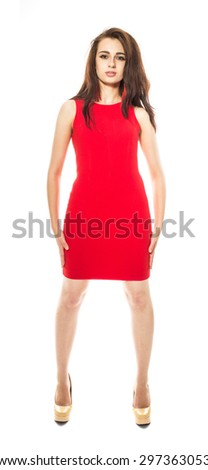Beautiful young brunette model with arms at side in red dress and yellow high heel shoes. Front view. Isolated on a white background. - stock photo