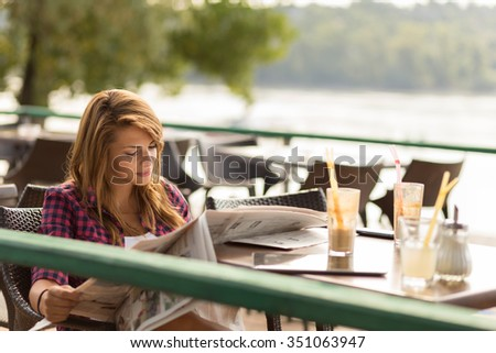 Beautiful young brunette sitting in a cafe, drinking coffee and reading newspapers - stock photo