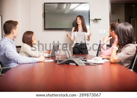 Beautiful young brunette speaking in front of her colleagues in a meeting room - stock photo