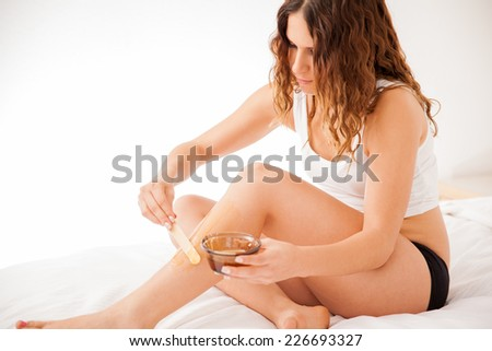 Beautiful young brunette spreading some hot wax on her legs to remove all hair - stock photo