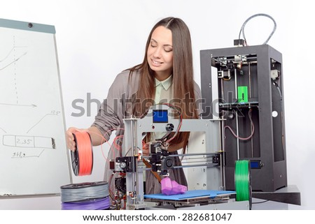 Beautiful young brunette student with long hair holding colorful plastic parts of a 3d-printer printing a new violet model in a laboratory  - stock photo