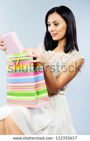 Beautiful young brunette taking out present from shopping bag - stock photo