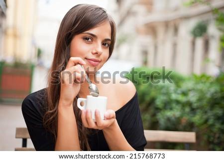 Beautiful young brunette tourist woman enjoying coffee. - stock photo