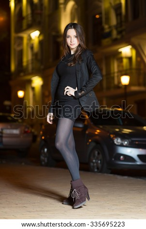 Beautiful young brunette wearing black clothes posing near the road - stock photo
