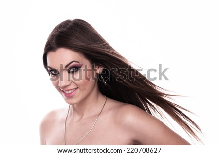 Beautiful young brunette with her hair fluttering on the wind, looking into camera, isolated on white  - stock photo