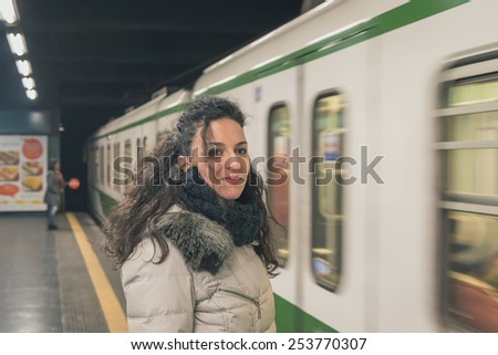 Beautiful young brunette with long curly hair posing in a metro station - stock photo