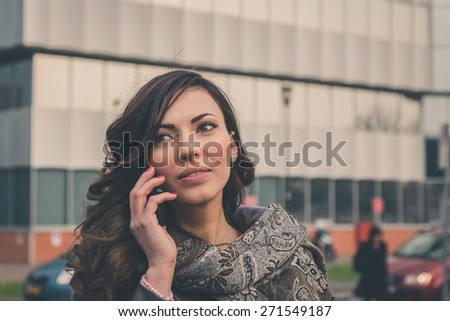 Beautiful young brunette with long hair talking on phone in an urban context - stock photo