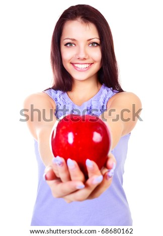 beautiful young brunette woman giving us a big red apple (focus on the face) - stock photo