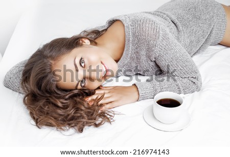 beautiful young brunette woman having a cup of coffee in bed at home - stock photo