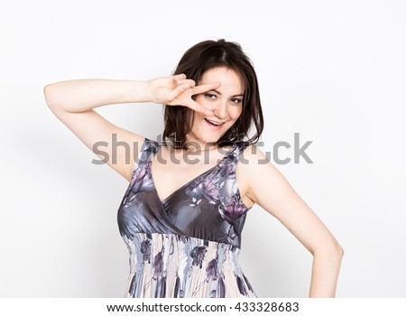 beautiful young brunette woman in a colorful dress posing and expresses different emotions. woman's hands shows various signs, disco. close-up portret - stock photo