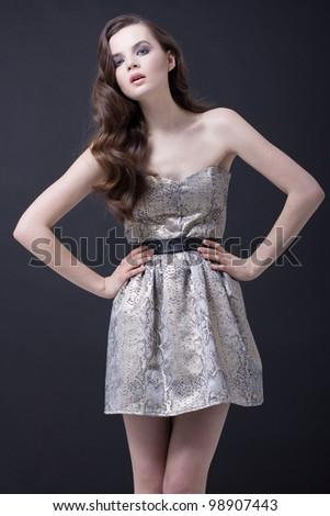Beautiful young brunette woman in fashion dress - stock photo