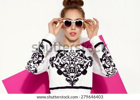 beautiful young brunette woman in funky skirt and sweatshirt, white sunglasses, bun, handbag posing in studio. Fashion photo - stock photo