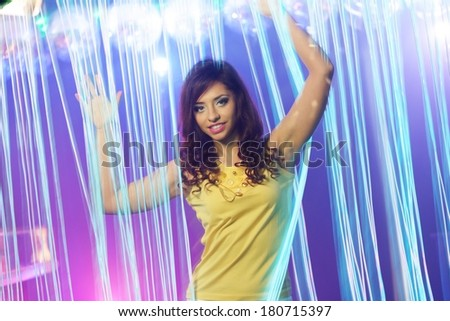 Beautiful young brunette woman in short skirt dancing at the night club  - stock photo