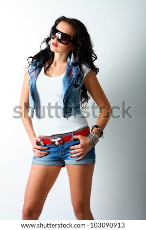 beautiful young brunette woman in style jeans cloth and sunglasses - stock photo