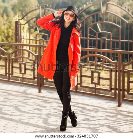 Beautiful young brunette woman in sunglasses and a hat walks through the city in the autumn sunny day. Lady dressed in a red coat, black jeans and boots - stock photo