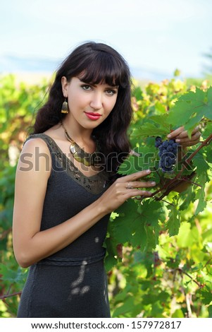 Beautiful young brunette woman in vineyard with a bunch of grapes - stock photo