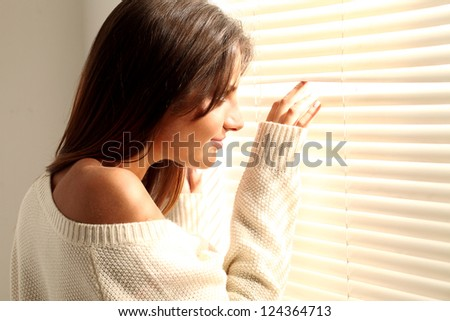 Beautiful young brunette woman in white near window - stock photo
