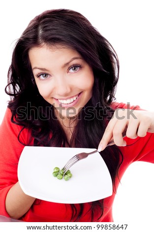 beautiful young brunette woman keeping a diet and eating peas at home - stock photo