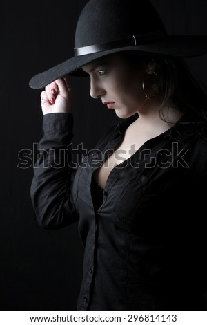 beautiful young brunette woman lady with a big breasts posing in a studio on a black background with old style hat - stock photo
