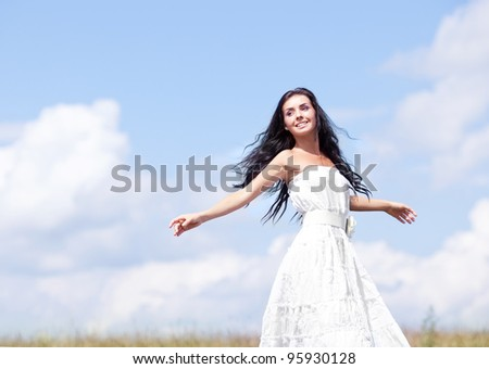 beautiful young brunette woman outdoor on the hill on a summer day, against blue sky with clouds - stock photo