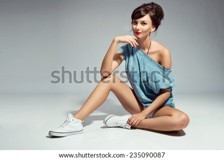 beautiful young brunette woman posing in a t-shirt and sneakers - stock photo