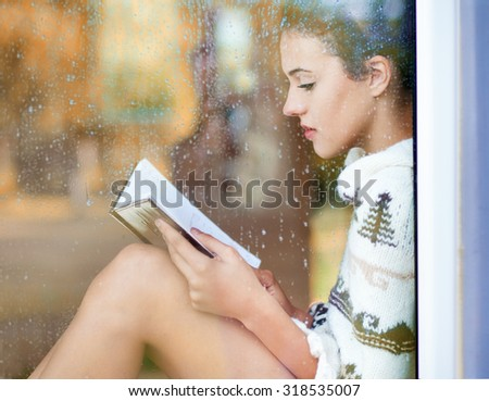 Beautiful young  brunette woman reading book wearing knitted dress sitting home behind a window covered with rain drops. Blurred fall garden reflection on the glass. Raining autumn concept - stock photo