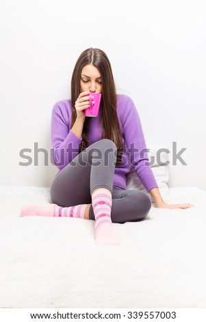 Beautiful young brunette woman sitting in bed at home drinking coffee or tea. Teenage girl relaxing drinking hot beverage, wearing winter loungewear. Medium retouch. - stock photo