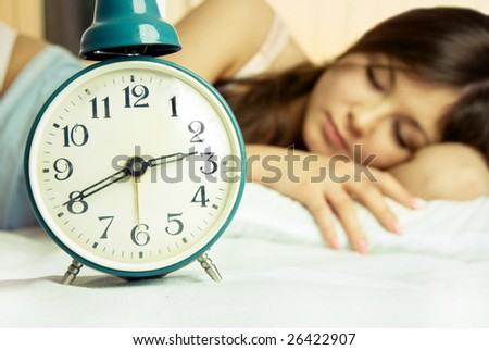 beautiful young brunette woman sleeping peacefully in bed with the alarm clock standing near her - stock photo