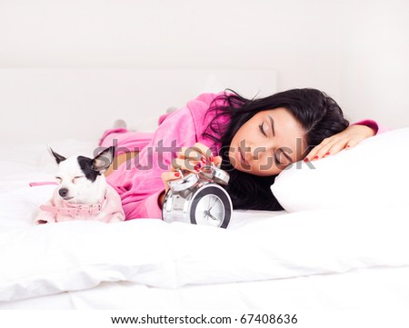 beautiful young brunette woman sleeping with her dog on the bed - stock photo