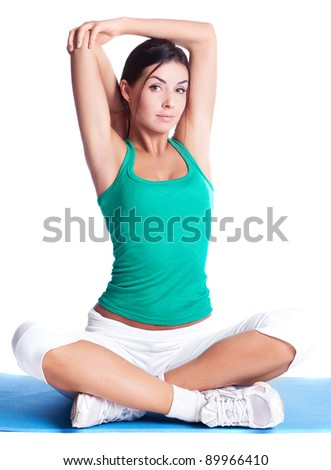 beautiful young brunette woman stretching the muscles of her arms, isolated against white background - stock photo
