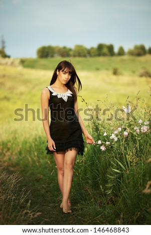 Beautiful young brunette woman walking in a field in a short black dress - stock photo