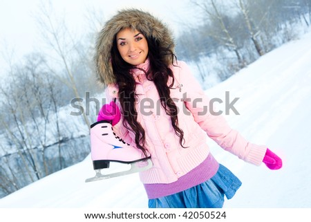 beautiful young brunette woman wearing warm winter clothes going to ice skating - stock photo
