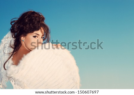 beautiful young brunette woman  with angel wings against blue sky,  outdoor shot, small amount of grain added - stock photo