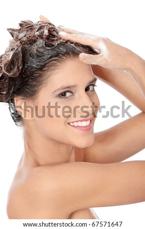 Beautiful young brunette woman with attractive smile soaping her head - isolated on white background - stock photo