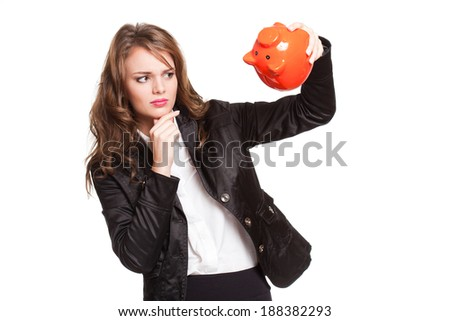 Beautiful young brunette woman with bright orange piggy bank. - stock photo