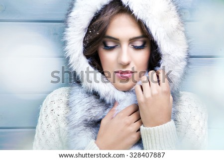 Beautiful young  brunette woman with eyes closed, wearing knitted sweater and fur hood, covered with snow flakes. Snowing winter beauty concept. - stock photo