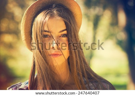 Beautiful young brunette woman with long hair flying in the wind and brown hat in park in summer. Head shot of gorgeous teenage girl with blue eyes. Retouched, filter, shallow depth of field. - stock photo