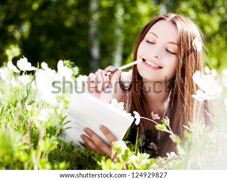 beautiful young brunette woman writing in her diary on the  meadow with white flowers - stock photo