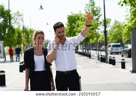 beautiful young business people man and woman waving a taxi cab in a public transportation station - stock photo