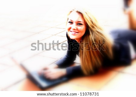 Beautiful young business student in the city typing on a laptop computer - stock photo