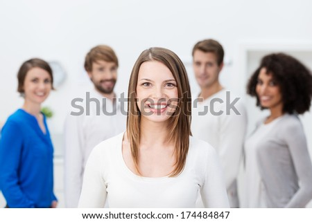 Beautiful young business team leader standing in front of her successful team smiling broadly at the camera confident in their success - stock photo