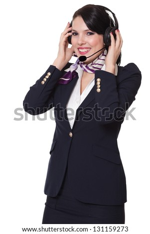 Beautiful young business woman dressed in a navy suit with a purple scarf and white shirt standing smiling and holding her earphones and microphone with both her hands, isolated on white background - stock photo