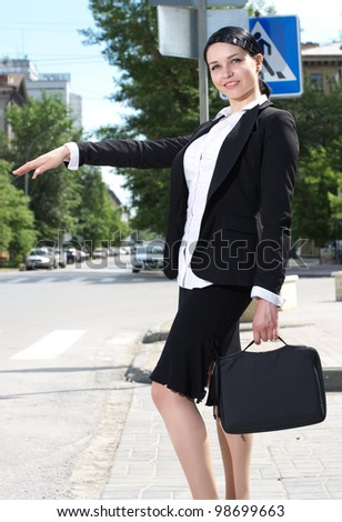 Beautiful young business woman hailing taxi cab in the city - stock photo