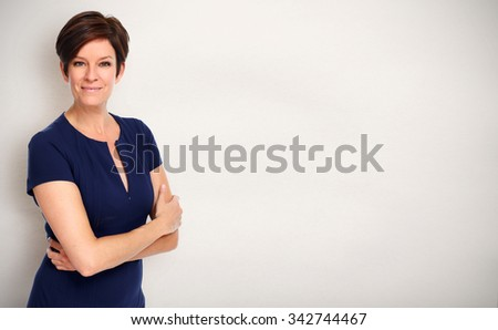 Beautiful young business woman over gray wall background. - stock photo
