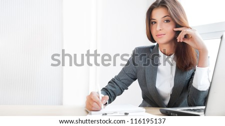 Beautiful young business woman sitting relaxed at her office and looking at camera - stock photo