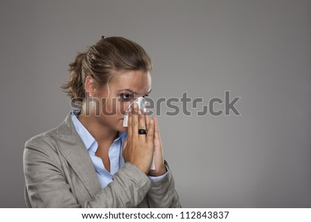 Beautiful young business woman with a cold blowing nose - stock photo