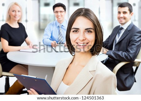 Beautiful young business woman with colleagues discussing in the background - stock photo