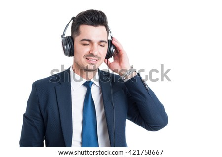 Beautiful young businessman enjoying music on headphones and relaxing in his freetime isolated on white background - stock photo
