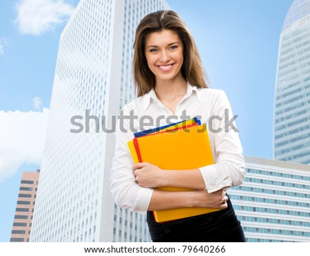 Beautiful young businesswoman among the skyscrapers of the modern business center - stock photo