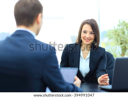 Beautiful young businesswoman conducting a job interview seated at her desk - stock photo